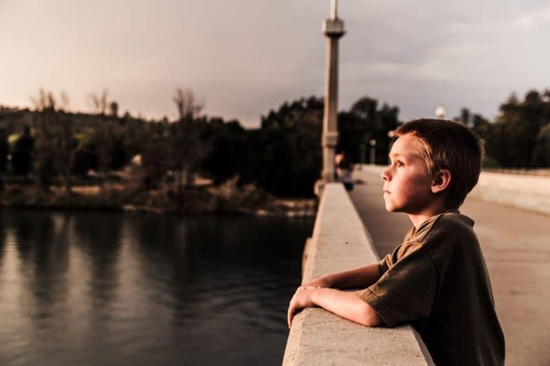 Eduquer Avec Sagesse - Photo by Japeth Mast on Unsplach jeune garcon sur le pont traversant un fleuve en train de reflechir en regardant au loin vers le haut