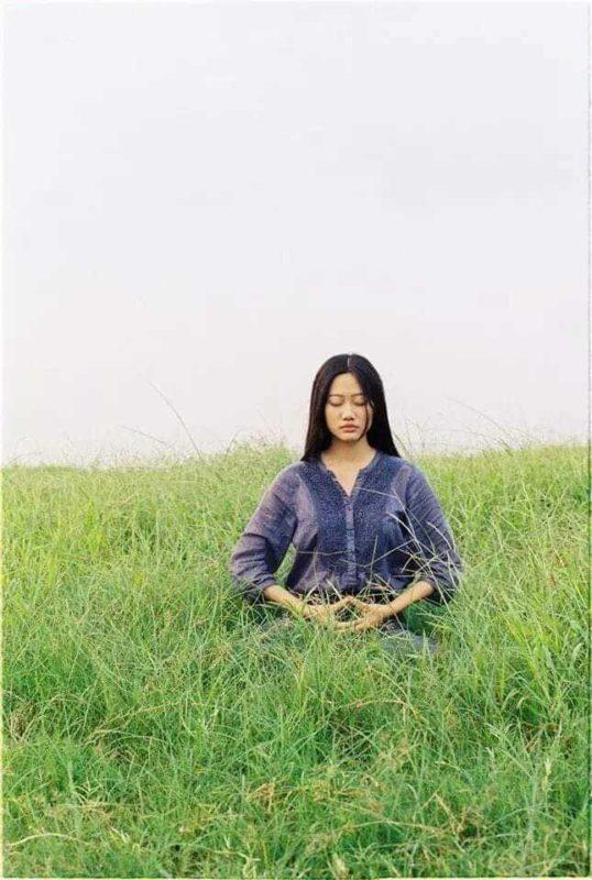 Eduquer Avec Sagesse femme dans l herbe qui pratique la meditation du Falun Dafa