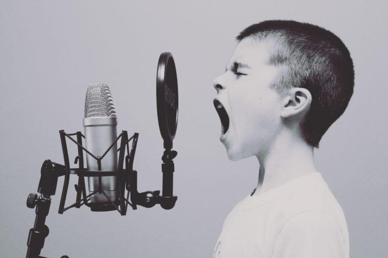 Eduquer Avec Sagesse - Photo by Jason Rosewell on Unsplash - jeune garçon de profil qui crie dans un micro noir et blanc