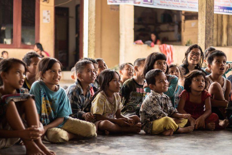 Eduquer Avec Sagesse - Photo by Yannis H on Unsplash - des enfants assis par terre en rond émerveillés captivés