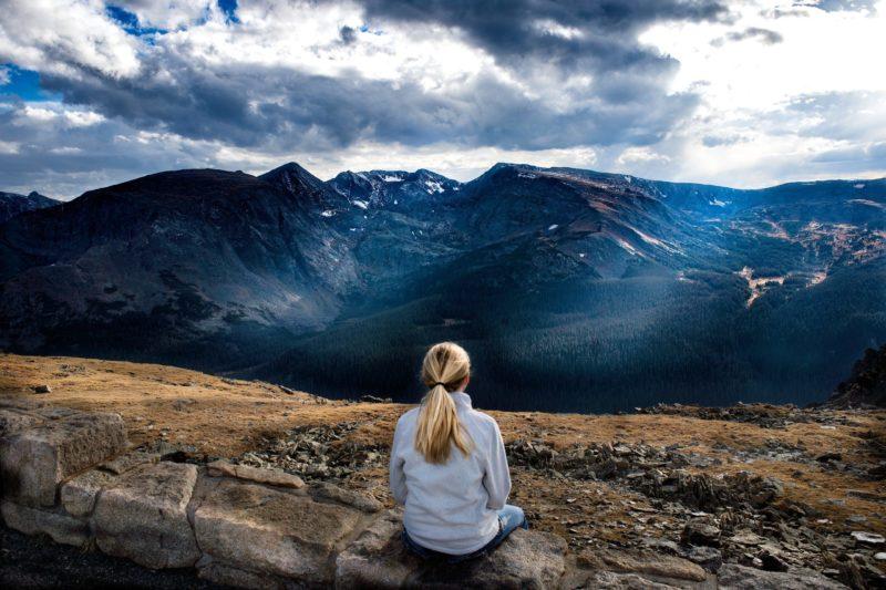 Eduquer Avec Sagesse - Photo by Donald Giannatti on Unsplash - jeune femme blonde en bleu de dos devant un paysage de montagne et ciel et nuages bleus en train de contempler