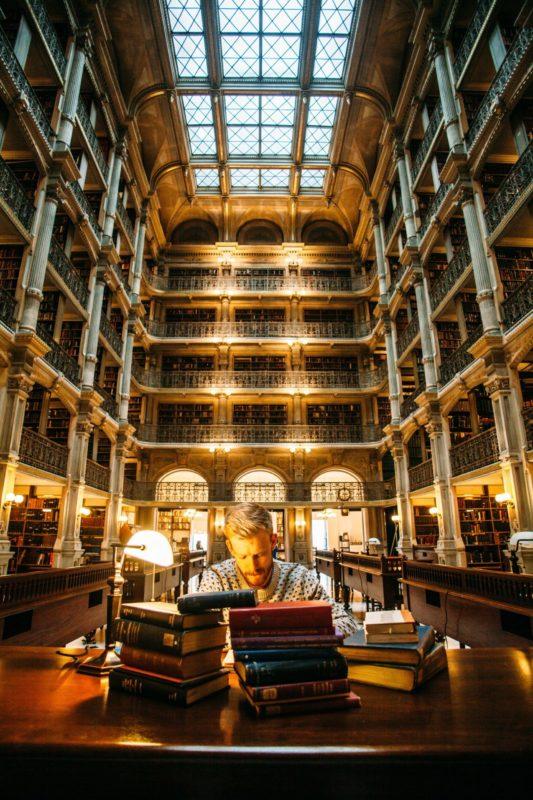 Eduquer Avec Sagesse Photo by Elijah Hail on Unsplash Homme lisant à la lumière d'une lampe de bureau dans une bibliothèque ancienne