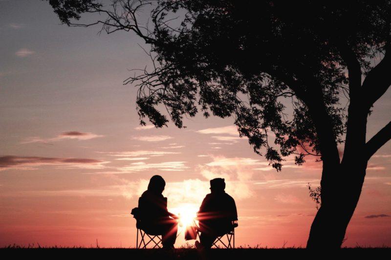 Eduquer Avec Sagesse Photo de Harli Marten deux personnes sous un arbre devant un coucher de soleil en contre jour en train de discuter