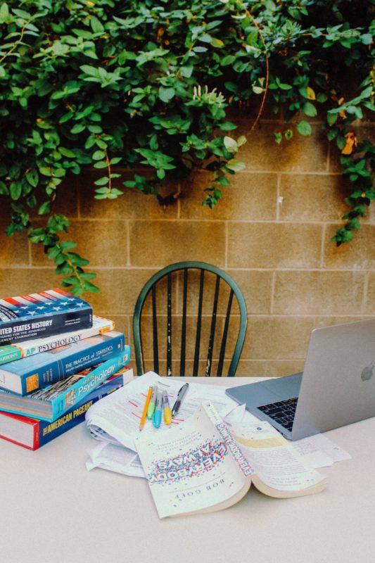 Eduquer Avec Sagesse - Photo by Jaeyoung Geoffrey Kang on Unsplash - chaise de jardin contre mur extérieur, table pile de cahier à côté d'un ordinateur