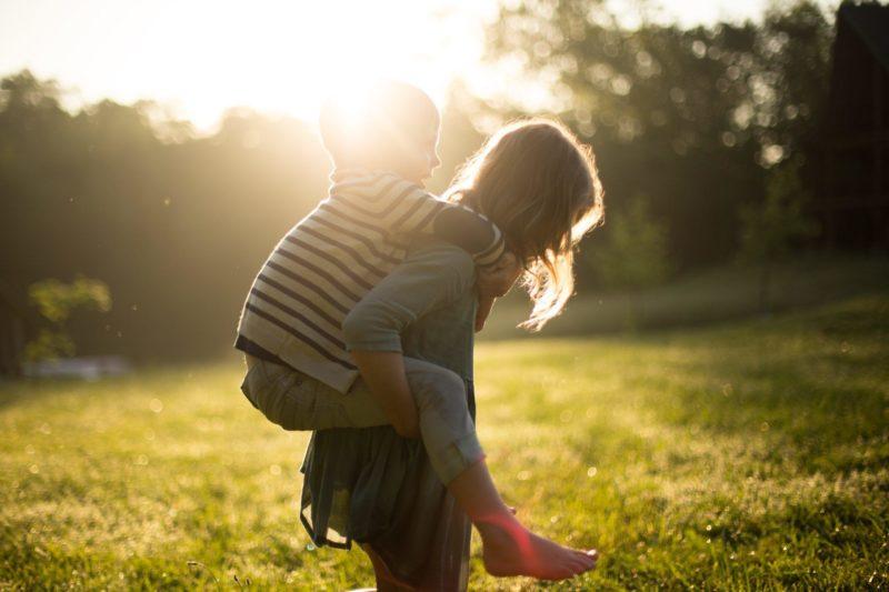 Eduquer Avec Sagesse - Photo by Jenn Evelyn-Ann on Unsplash - Une mère portant son enfant sur le dos, dans la nature, sur l'herbe, en contre jour