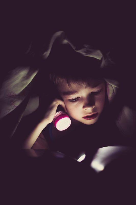 Eduquer Avec Sagesse - Photo by Klim Sergeev on Unsplash - Enfant sous une couverture la nuit qui lit à la lumière d'une lampe torche