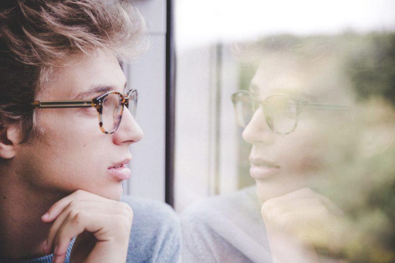 Eduquer AVec Sagesse - Photo by Laurenz Kleinheider on Unsplash- Jeune homme regardant par une fenetre avec son reflet dans la vitre