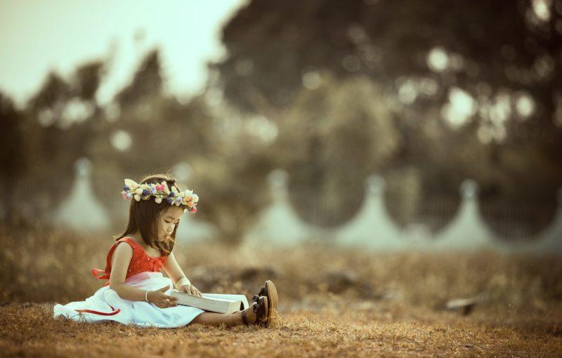 Eduquer Avec Sagesse Photo by MI PHAM on Unsplash Petite fille assise dans l'herbe avec une couronne de fleurs sur la tete en train de lire