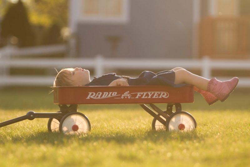 Eduquer Avec Sagesese - photo by lake-meyer-on unsplash - Jeune garçon allongé dans un chariot d'enfant, de profil, sur l'herbe