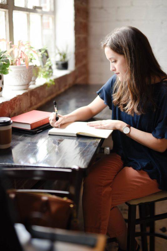 Eduquer Avec Sagesse photo by hannah-olinger Jeune femme écrivant à une table devant une fenêtre