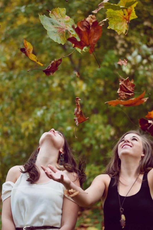 Eduquer avec sagesse - photo de evelyn-sur-unsplash-deux jeunes filles dans la nature jetant des feuilles d'automne en regardant vers le ciel
