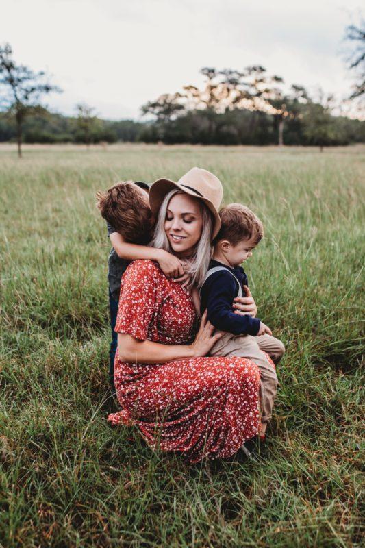 Eduquer Avec Sagesse - photo de jessica-rockowitz-sur-unsplash-maman et ses deux enfants sur fond de nature et d herbe