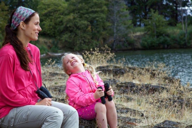Eduquer Avec Sagesse - Mere et fille au bord de l eau - petite fille tenant des jumelles et renversant la tete vers sa mere
