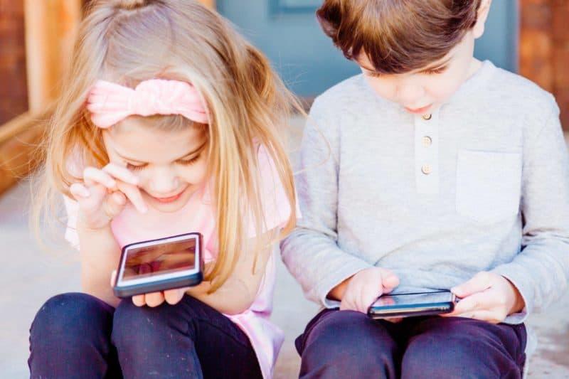 fille et garçon tete baissée sur des ecrans mobiles eduquer avec sagesse
